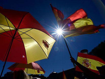 Manifestantes portan banderas y paraguas de la bandera de España.