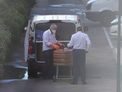 Dos operarios trasladan féretros de la Residencia de mayores Domusvi, este jueves en Valdemoro. EFE/JuanJo Martín