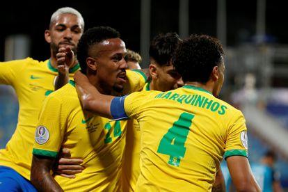 Brazil players celebrate Militão's goal.