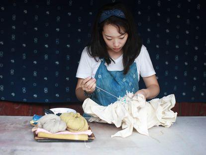 La artista china Lin Fanglu, ganadora del Craft Prize 2021, trabaja en su obra 'SHE'.