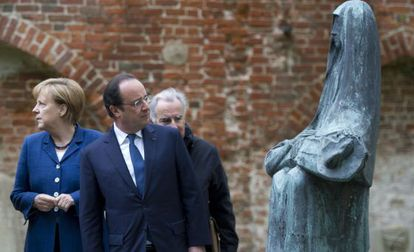 El presidente francés François Hollande mira una escultura durante una visita junto a Angela Merkel a un convento en Stralsund, al noreste de Alemania.