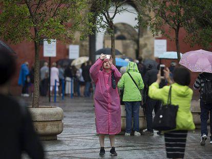 Turistas bajo la lluvia el viernes en el centro de Sevilla.