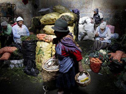 Una mujer transporta alimentos en el interior del mercado de San Roque.