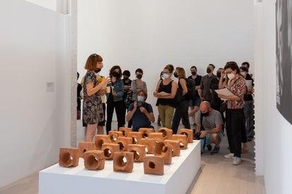Nuria Güell delante de las piezas de barro con los impactos de bala de la obra 'El síndrome de Sherwood 2', en Fabra i Coats.