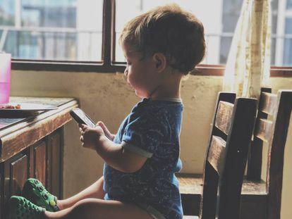 Un bebé mira un móvil con curiosidad.