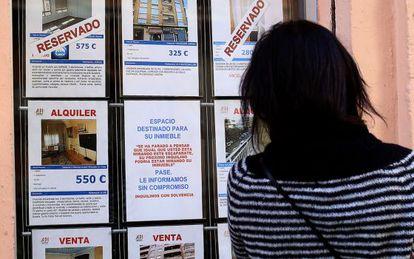 Una mujer mira el escaparte de una inmobiliaria en Valencia, en una imagen de archivo.