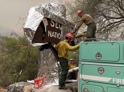 Tres bomberos cubrieron un cartel de madera con aluminio este viernes en California.