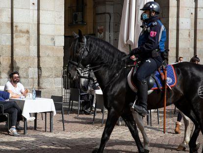Un agente pasa a caballo junto a los clientes de una terraza de la Plaza Mayor de Madrid, que no llevan la mascarilla obligatoria.