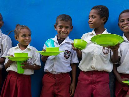 Un grupo de estudiantes esperan a entrar al comedor de su escuela.
