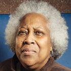 """Sharon Malcom, 67 años. Trabaja como bibliotecaria de una escuela en Baltimore y nunca se ha sentido discriminada por llevar su pelo natural. Cuando era joven se hizo la permanente. """"En esa época era lo natural para conseguir un trabajo, pero las cosas han cambiado"""". Hace 30 años abandonó los productos químicos y se dejó rastras. Ahora luce un 'look' afro. """"Nunca me he sentido discriminada porque siempre he trabajado en [el sector de la] educación, donde no es un problema""""."""
