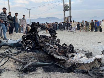 Un grupo de personas se concentran en el lugar donde estalló un coche cerca de un colegio de niñas en Kabul.