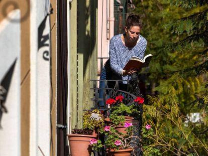 Una mujer lee un libro en el balcón de su casa, durante el confinamiento, en Barcelona.