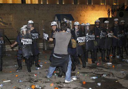 Un manifestante se enfrenta a la policía griega frente a la sede del Parlamento.