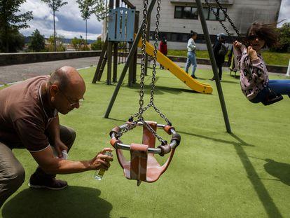 Niños juegan en un parque infantil de Santiago de Compostela, tras su apertura en la nueva normalidad. Un adulto desinfecta un columpio.