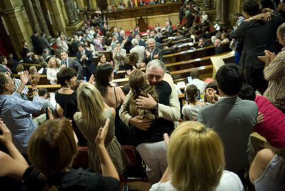 Público y diputados se felicitan en el Parlamento de Cataluña tras la aprobación de la ley.