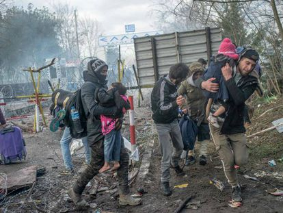Unos padres protegen a sus hijos de los botes lacrimógenos lanzados por la policía griega, este sábado en Pazarkule.