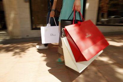 Dos personas con bolsas de marcas de lujo, en Madrid.