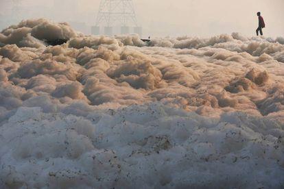 El pasado diciembre un hombre cruza en la India Yamuna, altamente contaminado por residuos tóxicos.