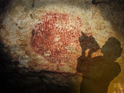 Proyección de la sombra de una persona mientras sopla la concha encontrada en la cueva decorada de Marsoulas, en Francia.