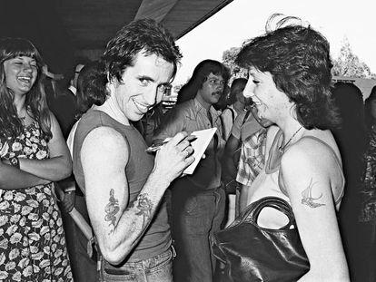 Bon Scott firma un autógrafo a una admiradora en Sidney en 1976, cuatro años antes de su muerte.