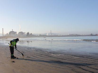 Los propios pescadores se encargan de limpiar las trazas de carbón que deja la actividad de las industrias en la playa.