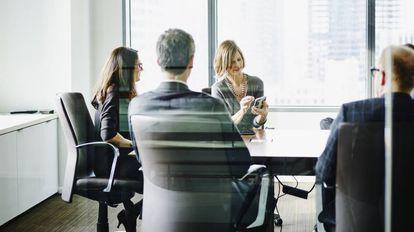 Dos ejecutivas presentan su proyecto a sus colegas en una reunión de trabajo.