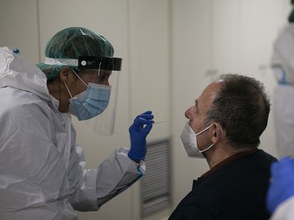 Una sanitaria toma una muestra para un test de antígenos en un punto de cribaje masivo en un barrio de Barcelona.