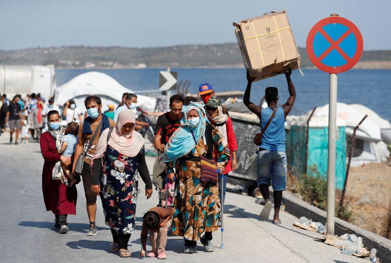Refugiados del campo incendiado en Moria caminan hacia un campamento temporal el pasado lunes en Lesbos, Grecia