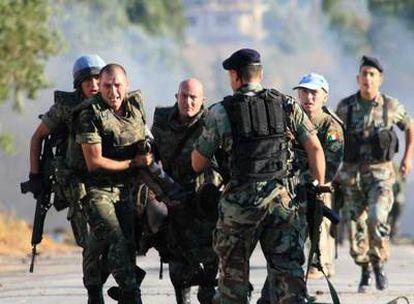 Soldados españoles trasladan a una de las víctimas del ataque con coche bomba en el pueblo de Jiam, al sur de Líbano.