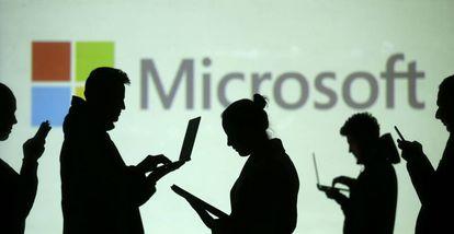 Usuarios con sus portátiles delante del logo de Microsoft
