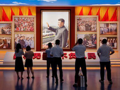 PUn grupo de personas miran imágenes del presidente chino, Xi Jinping, en el Museo de Historia del Partido Comunista de China recién inaugurado en Pekín