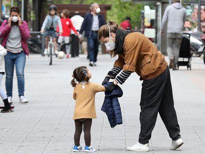 Una madre atiende a su hija mientras pasean por una calle de Madrid el pasado domingo.