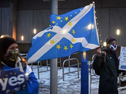 Un manifestante ondea frente al Parlamento Escocés una bandera con una mezcla de la escocesa y de la de la UE, la noche del 31 de diciembre.