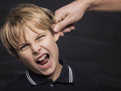 Un padre tira de la oreja a su hijo.