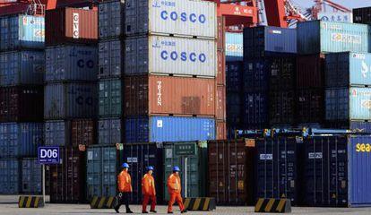 Tres trabajadores frente a varios contenedores de transporte en el puerto de Qingdao, este de China.