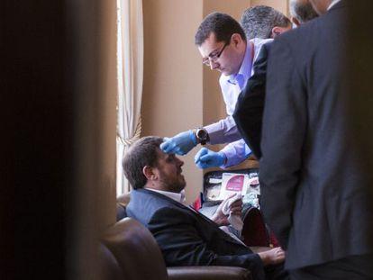 Junqueras es atendido tras su caída en el Parlament.