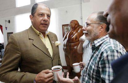El candidato del PAC, Luis Guillermo Solís, habla con unos periodistas.