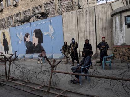 Un grupo de talibanes monta guardia en Kabul ante un cartel que representa a una mujer y a una niña.