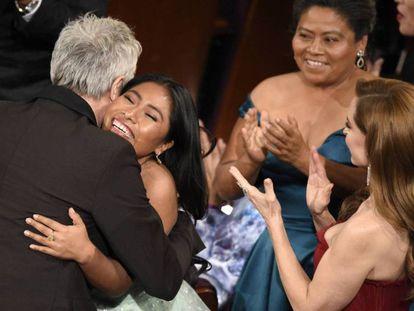Alfonso Cuarón abraza a Yalitza Aparicio en presencia de Marina de Tavira (a la derecha) tras ganar el Oscar.