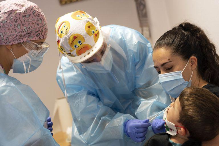 Elena (centro) y Mónica realizan una PCR a uno de los hijos de Gregorio Rincón, vecino de Azuqueca. / LUIS DE VEGA