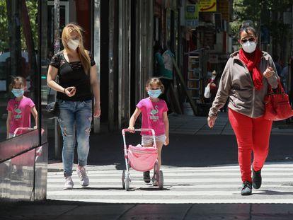 Adultos y niños pasean con mascarillas en Madrid.