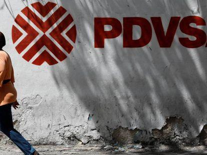 Una mujer camina frente al logo de la petrolera venezolana PDVSA en Caracas. En vídeo, declaraciones de Wilbur Ross.
