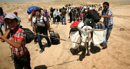 Refugiados sirios cruzan la frontera con el Kurdistán irakí.