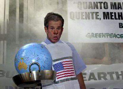 Un militante de Greenpeace con una careta de Bush y un globo terráqueo en una sartén, ayer en Sâo Paulo.