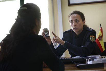 Una agente explica a una maltratada cómo usar el teléfono de emergencia.