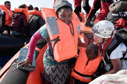 Una migrante y su hijo son rescatados por miembros de SOS Mediterranée y MSF este lunes frente a Libia.