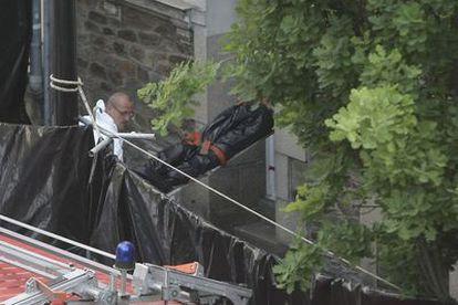 Miembros de la policía que investiga el caso sacan uno de los cuerpos encontrados de la casa de la familia desaparecida en Nantes.