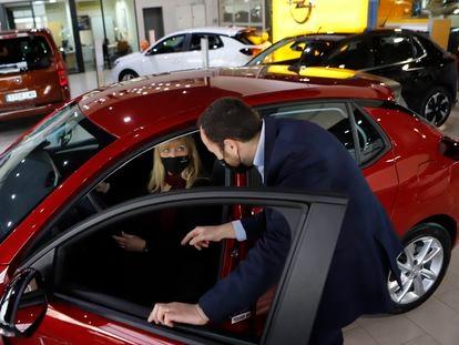Un vendedor muestra el interior de un vehículo a una clienta.