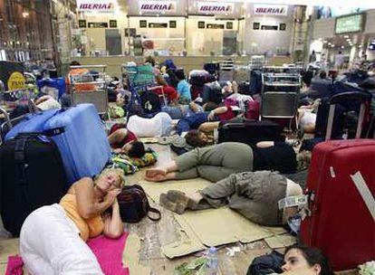 Viajeros duermen en El Prat tras el cierre del aeropuerto en julio.