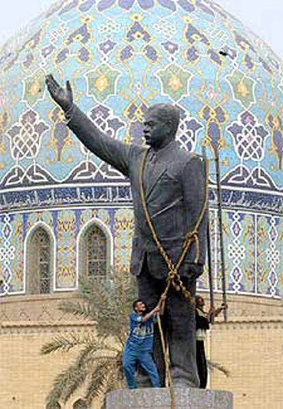 Dos bagdadíes encaramados a una estatua de Sadam, a la que han colocado una cuerda para derribarla.
